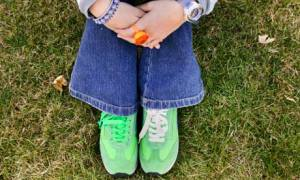 Arms and legs of girl sitting on grass