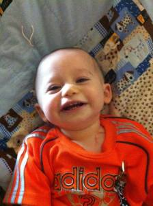 Sweet Xander smiling during his first few weeks of treatments, sitting on a prayer blanket made for him by a friend.